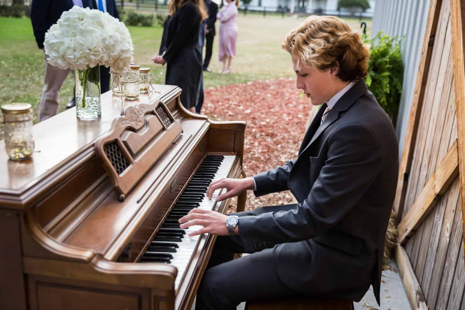 Young man playing piano for an article on wedding cost cutting tips
