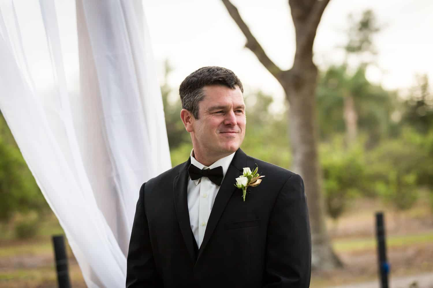 Groom waiting for bride during ceremony for an article on wedding cost cutting tips