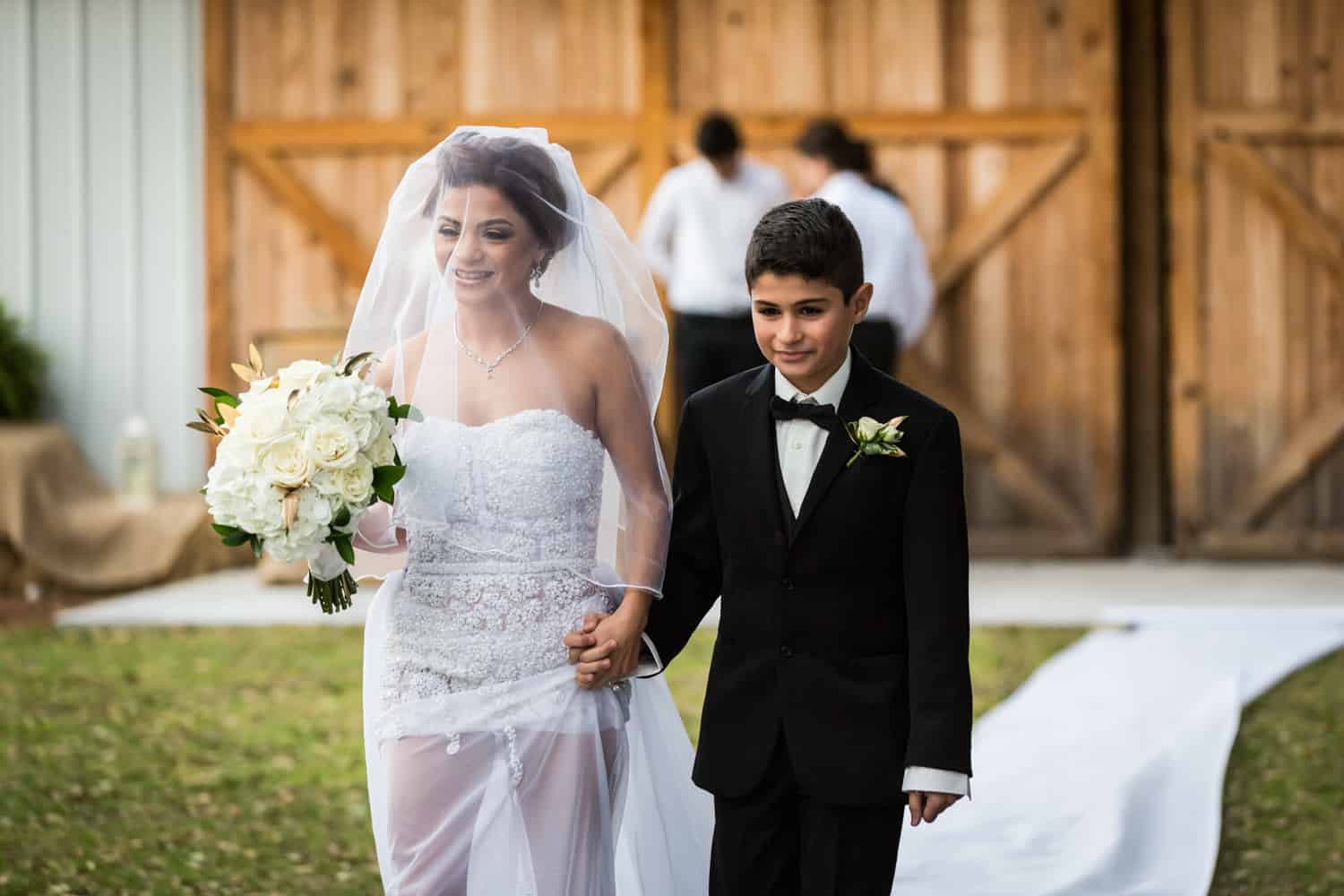 Bride and son walking down aisle during ceremony for an article on wedding cost cutting tips