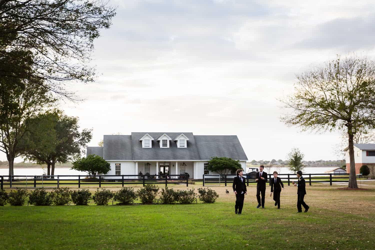 Young groomsmen playing outdoors in front of house for an article on wedding cost cutting tips