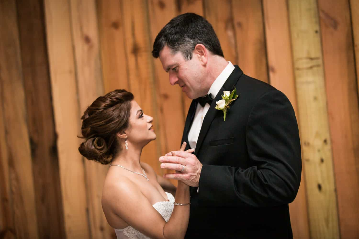Bride and groom in front of wood wall during first dance