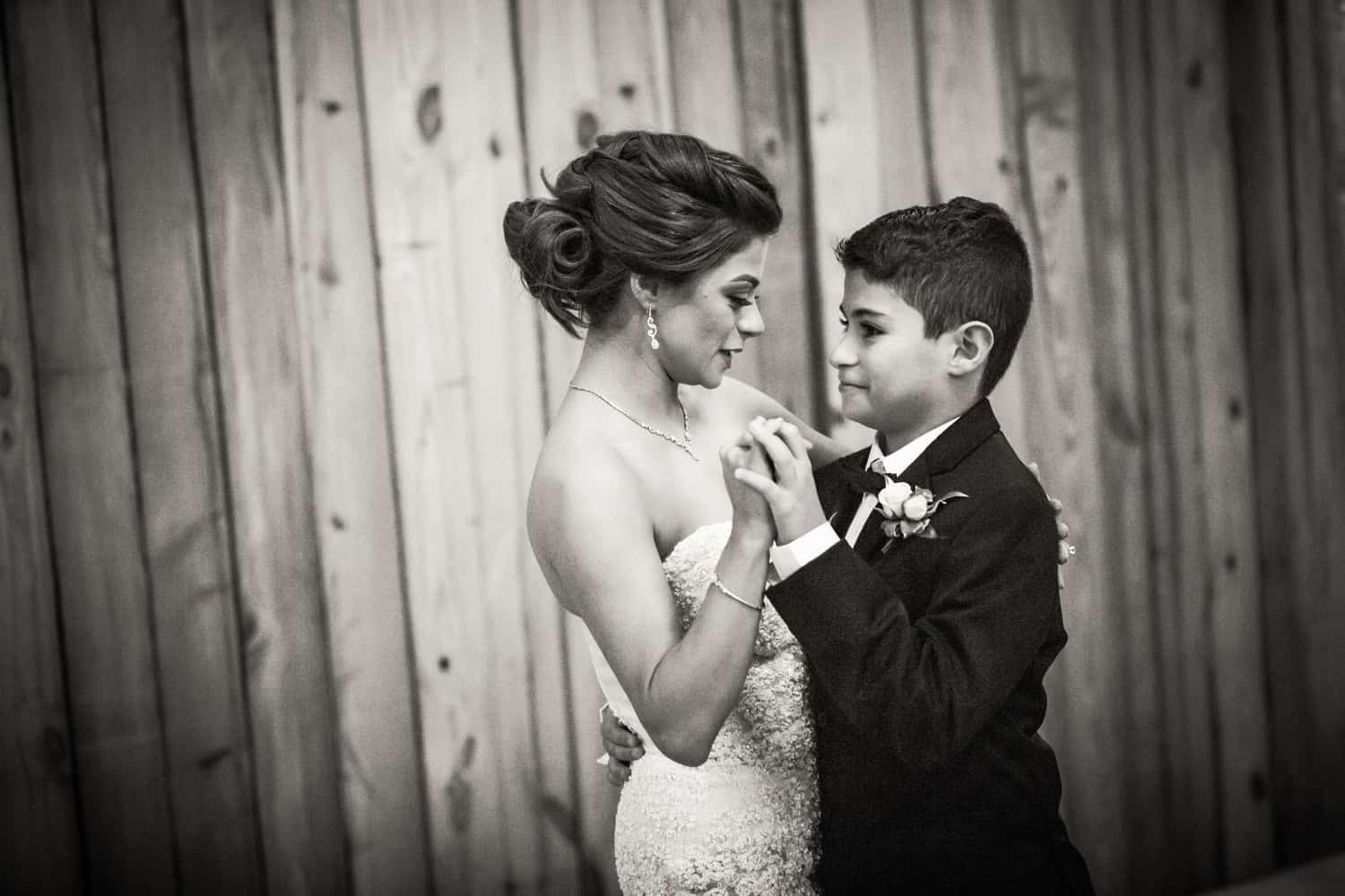 Black and white photo of bride dancing with son