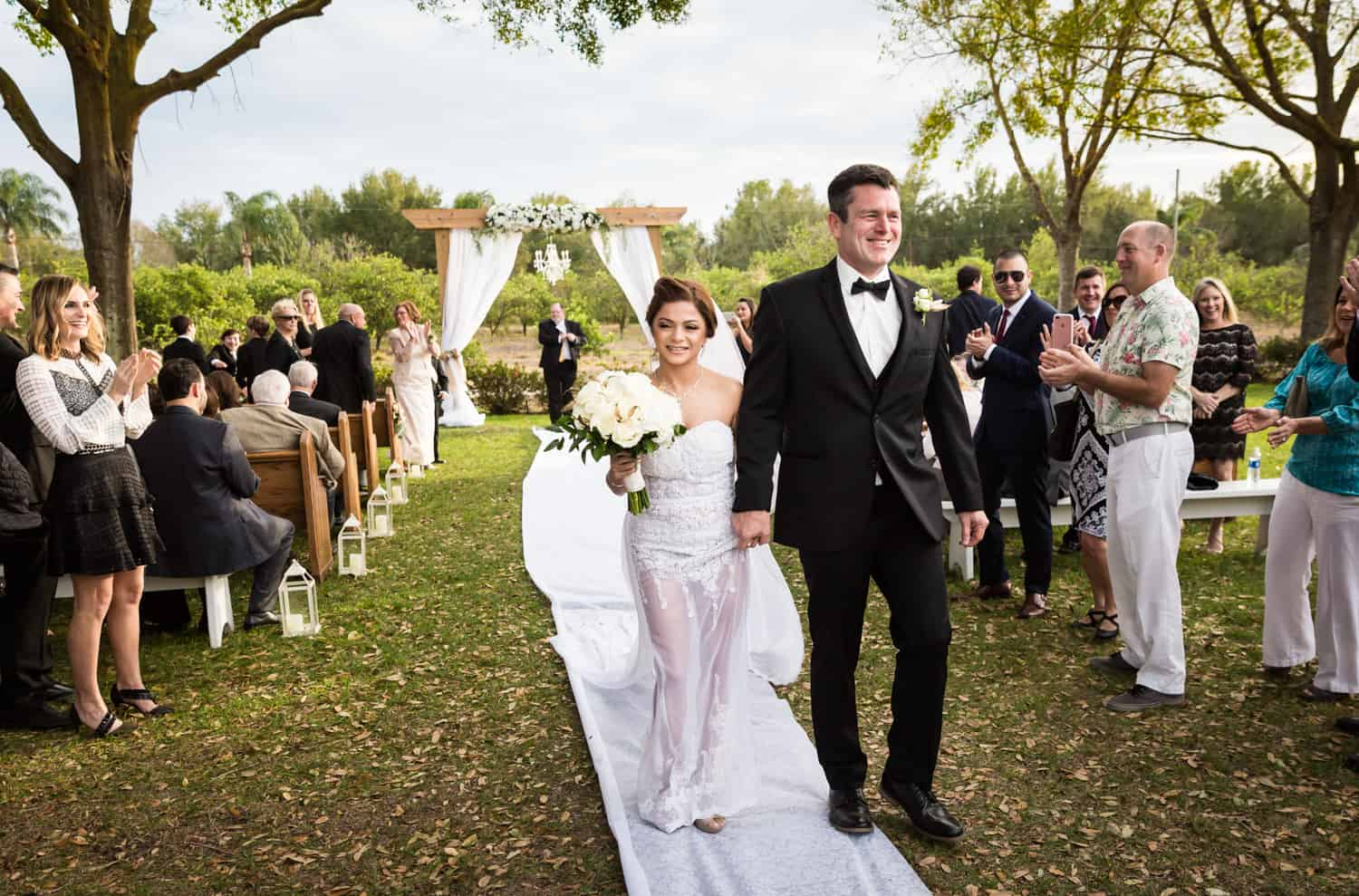 Bride and groom walking down aisle after ceremony for an article on wedding cost cutting tips