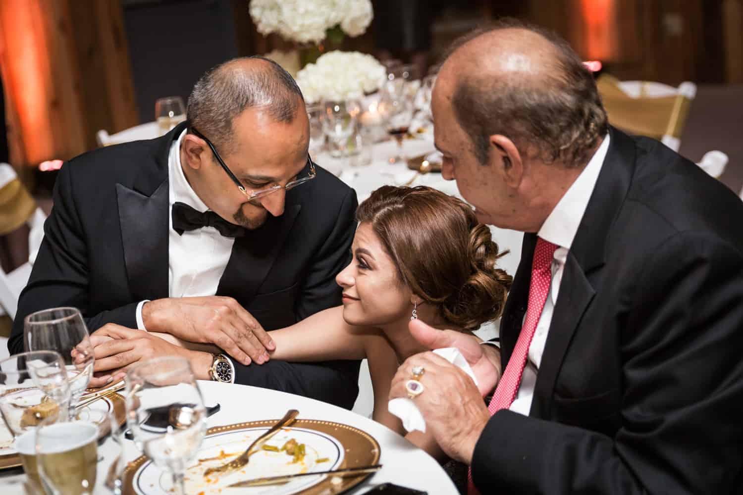 Bride talking with two men at table during Florida wedding reception