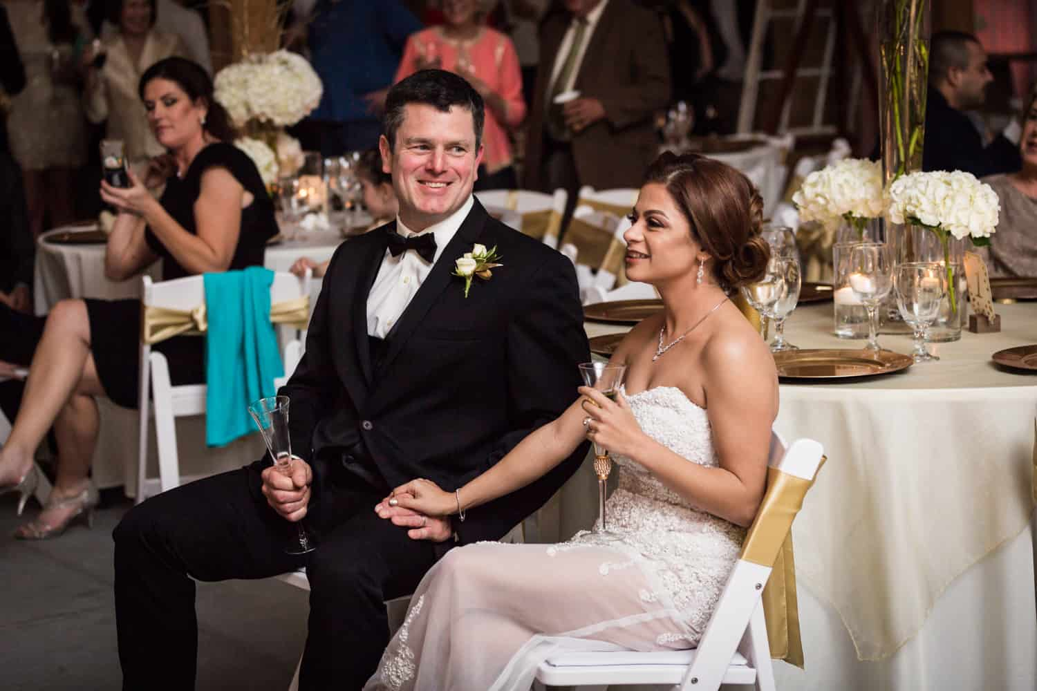Bride and groom listening to speeches during Florida wedding reception
