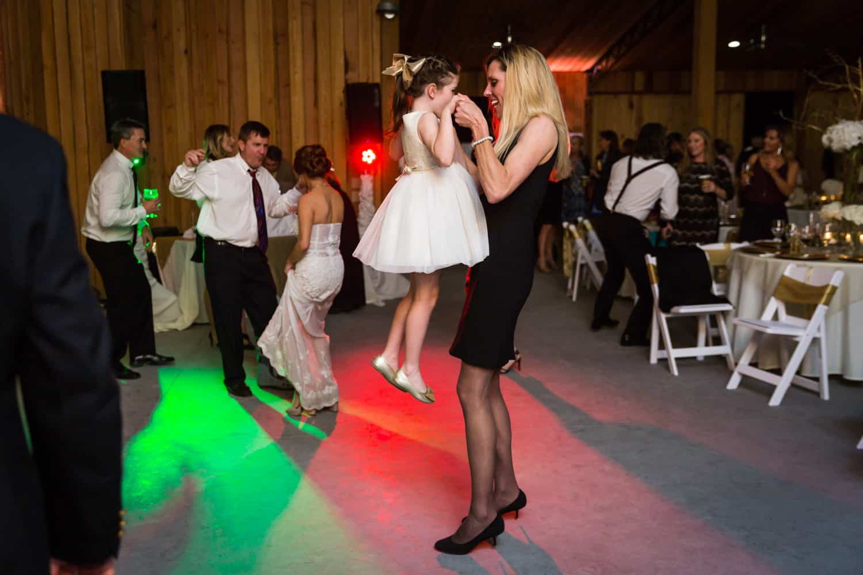 Woman lifting little girl on dance floor