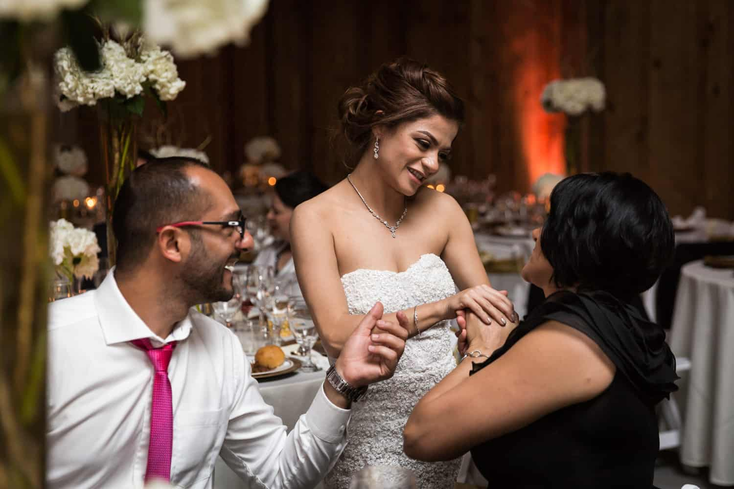 Bride chatting with couple at table