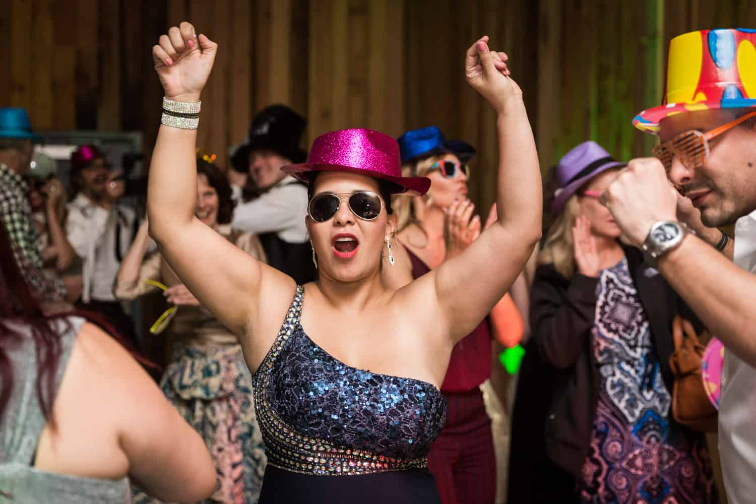 Woman wearing hat and sunglasses dancing with hands in air