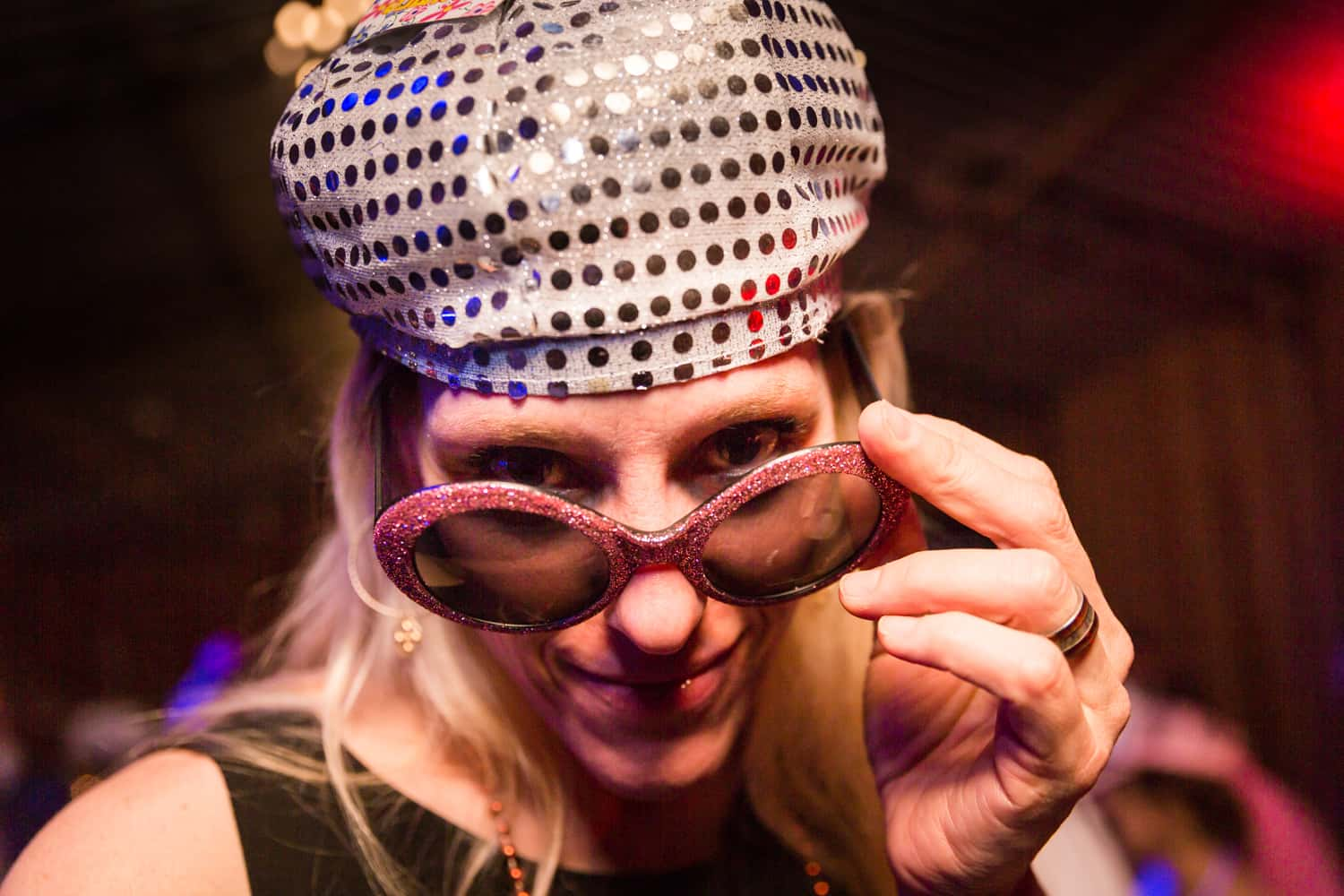 Woman wearing sequined hat and lowering sunglasses to camera