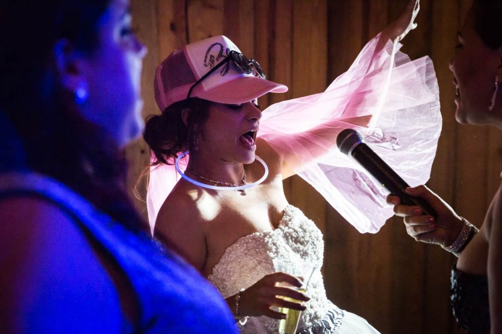 Bride wearing trucker hat and singing into microphone