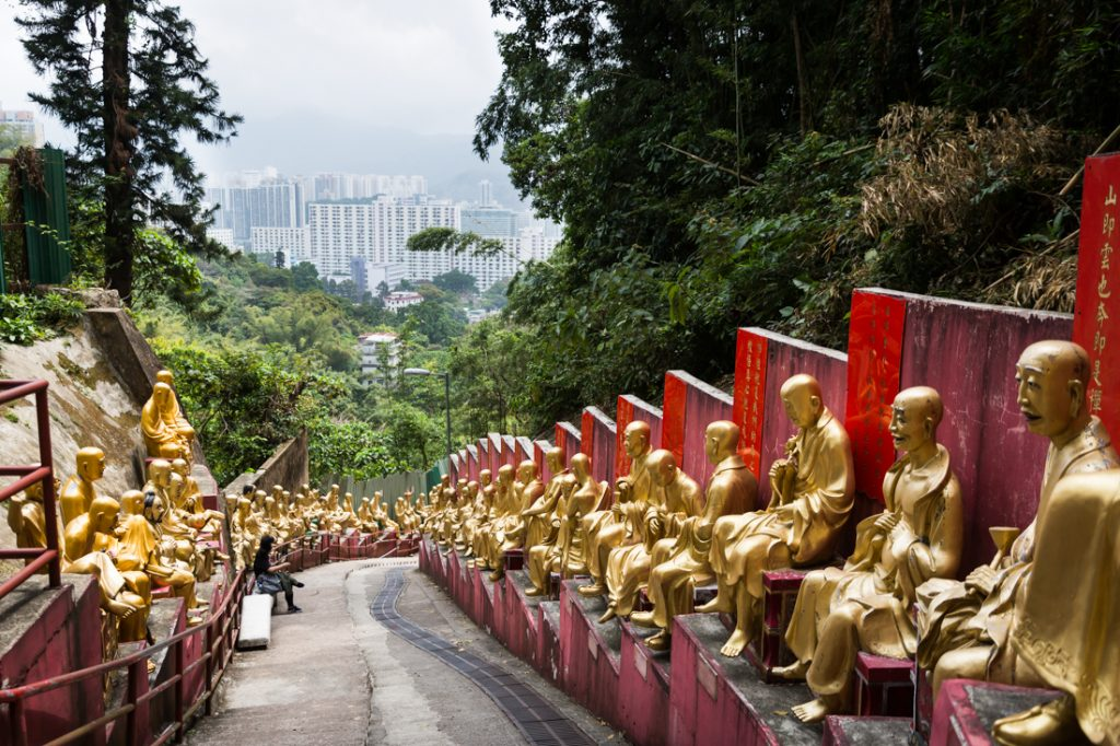 Line of golden buddha sculptures in the Ten Thousand Buddhas Monastery in Hong Kong