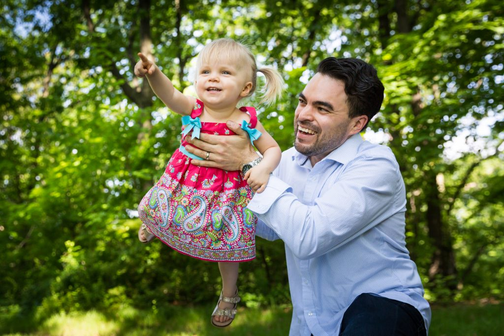 Father holding up little girl in Forest Park during family portrait session