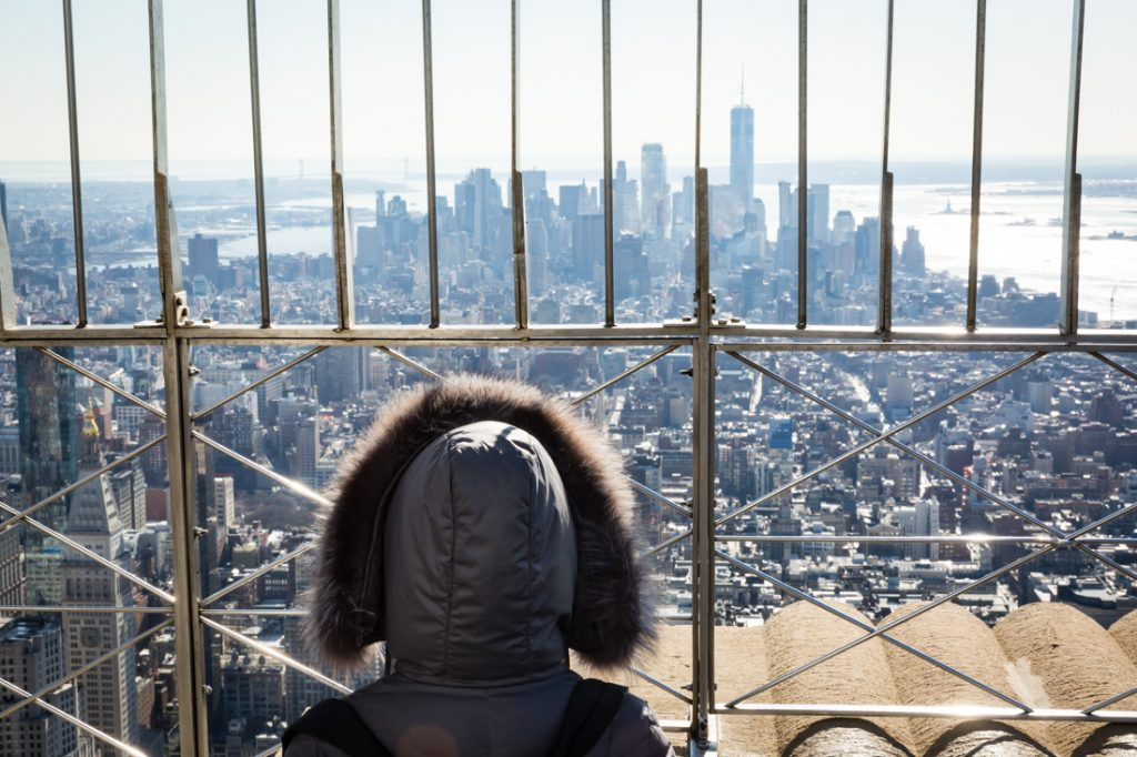 Person wearing fur hood looking at view of NYC from top of Empire State Buillding
