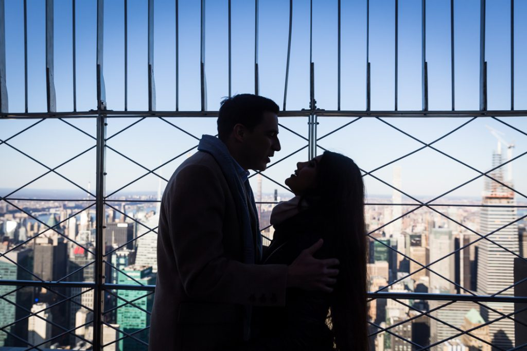 Couple about to kiss in silhouette on platform of Empire State Building