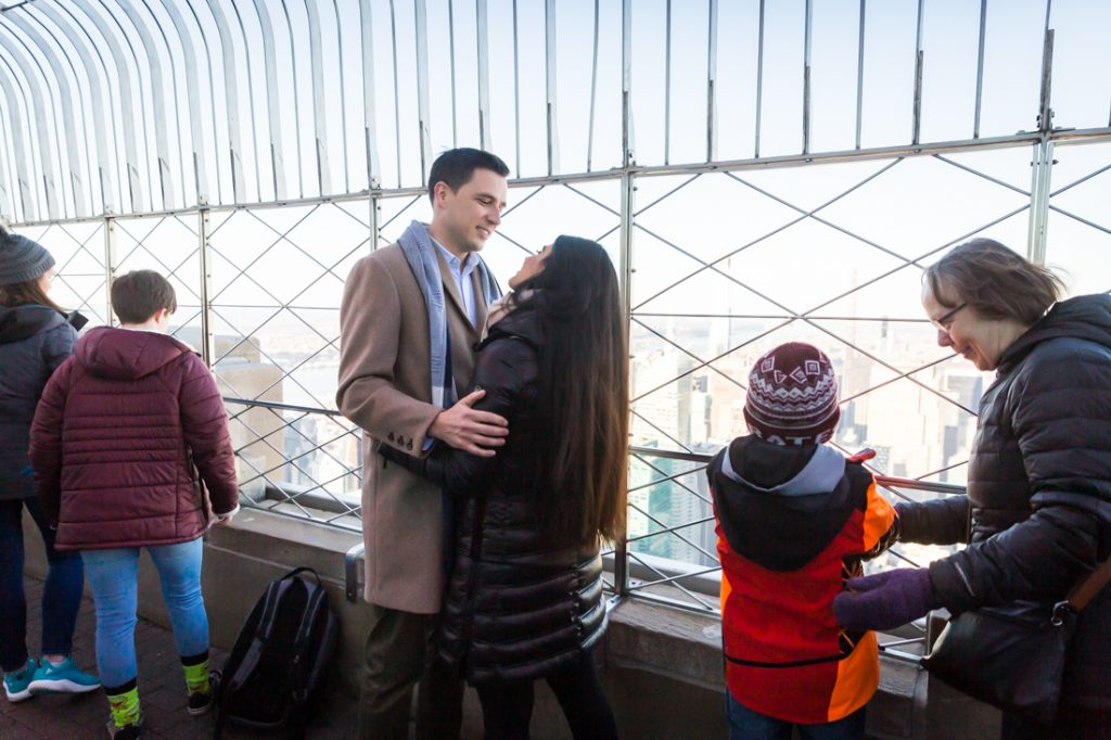 Couple hugging on platform before proposal on top of the Empire State Building