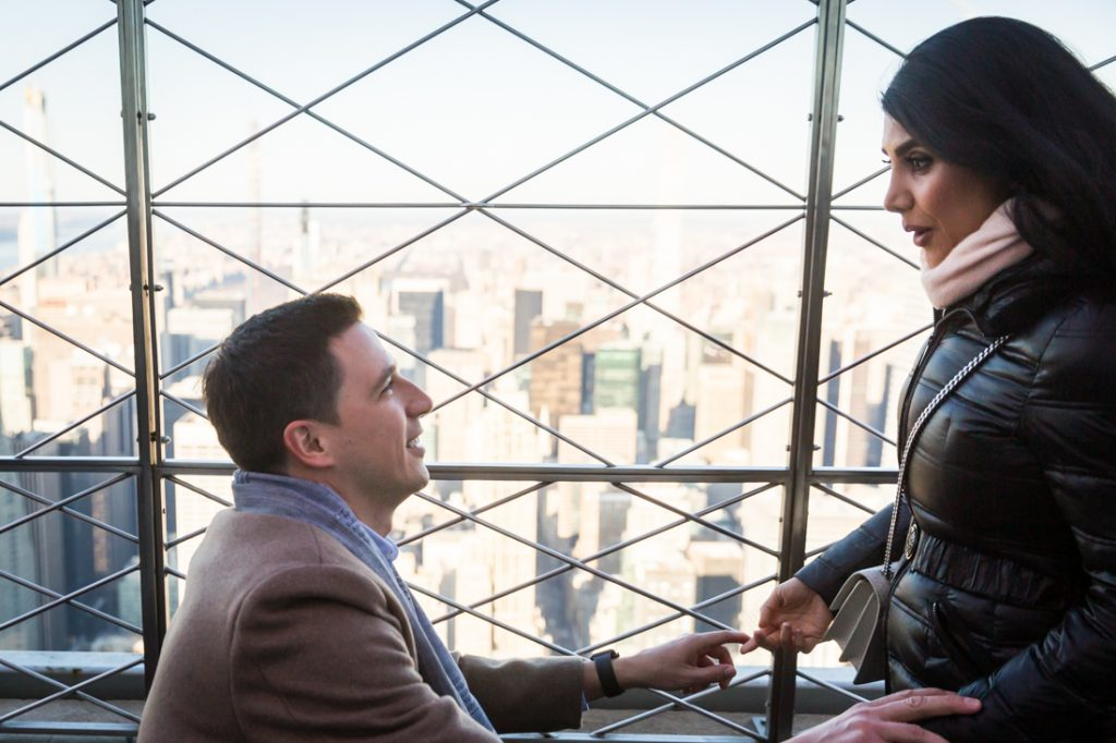 Man on one knee proposing to woman during proposal on top of the Empire State Building