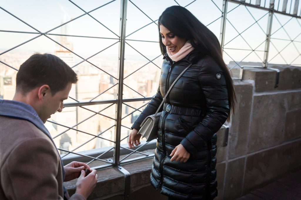 Woman looking surprised during proposal on top of the Empire State Building