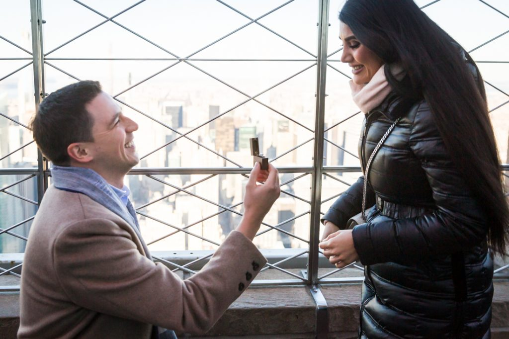 Man on one knee holding ring in front of woman during proposal on top of the Empire State Building