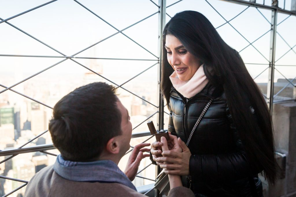Woman looking down at man on one knee during proposal on top of the Empire State Building
