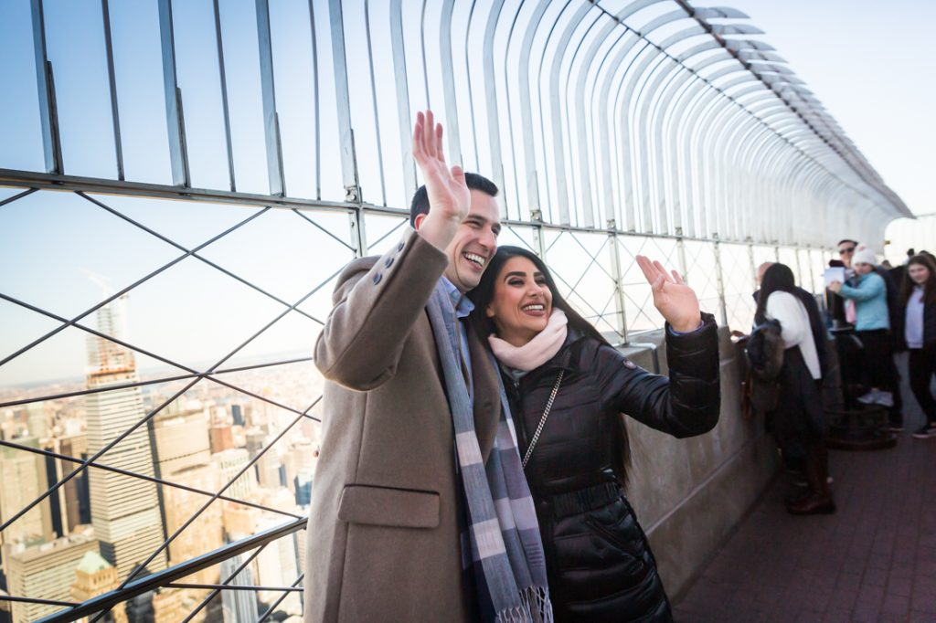 Couple waving to strangers in the window after proposal on top of the Empire State Building
