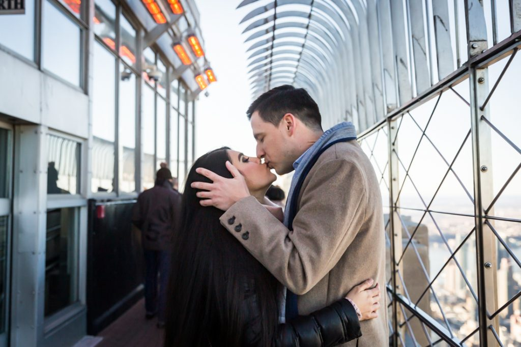 Couple kissing after proposal on top of the Empire State Building