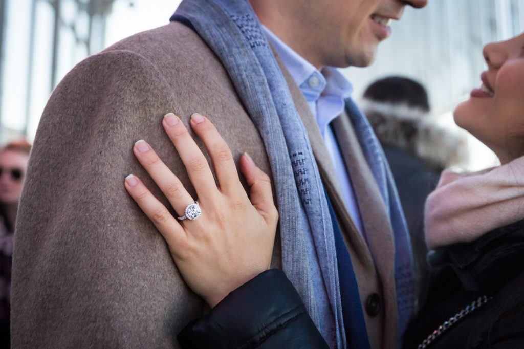 Close up of woman's hand with large engagement ring on man's jacket