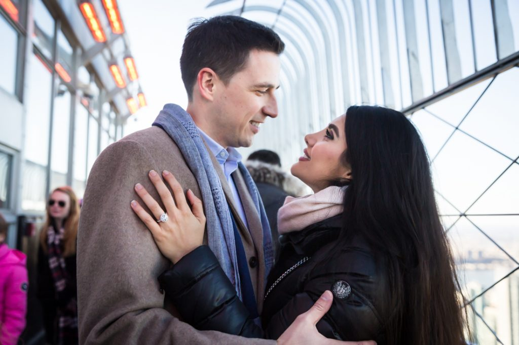 Couple together with woman's hand with large engagement ring on man's jacket