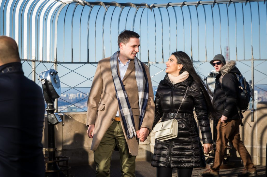 Couple walking on 86th floor viewing platform of Empire State Building