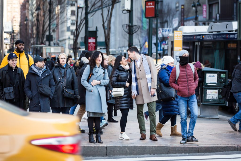Couple kissing on the corner of 34th Street and Sixth Avenue in Manhattan