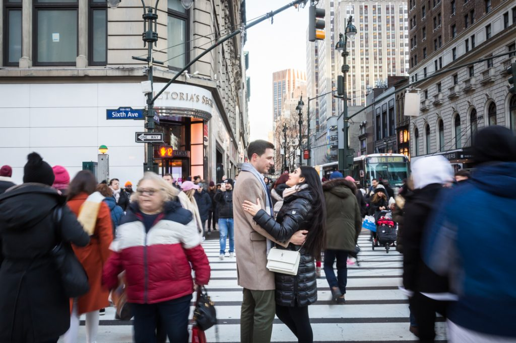 Couple hugging in the middle of crosswalk with blur of strangers