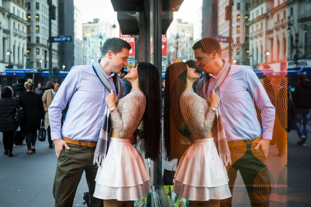 Reflection of couple kissing in storefront windows of Macy's in Herald Square