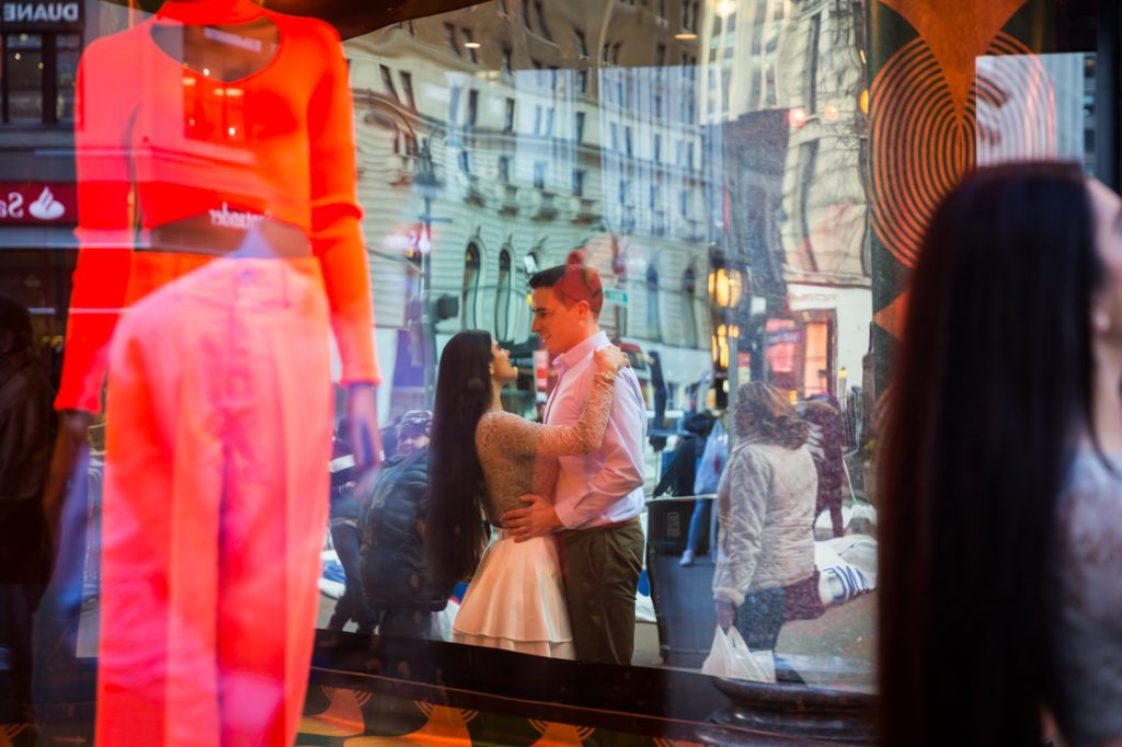 Reflection in Macy's storefront window of couple hugging