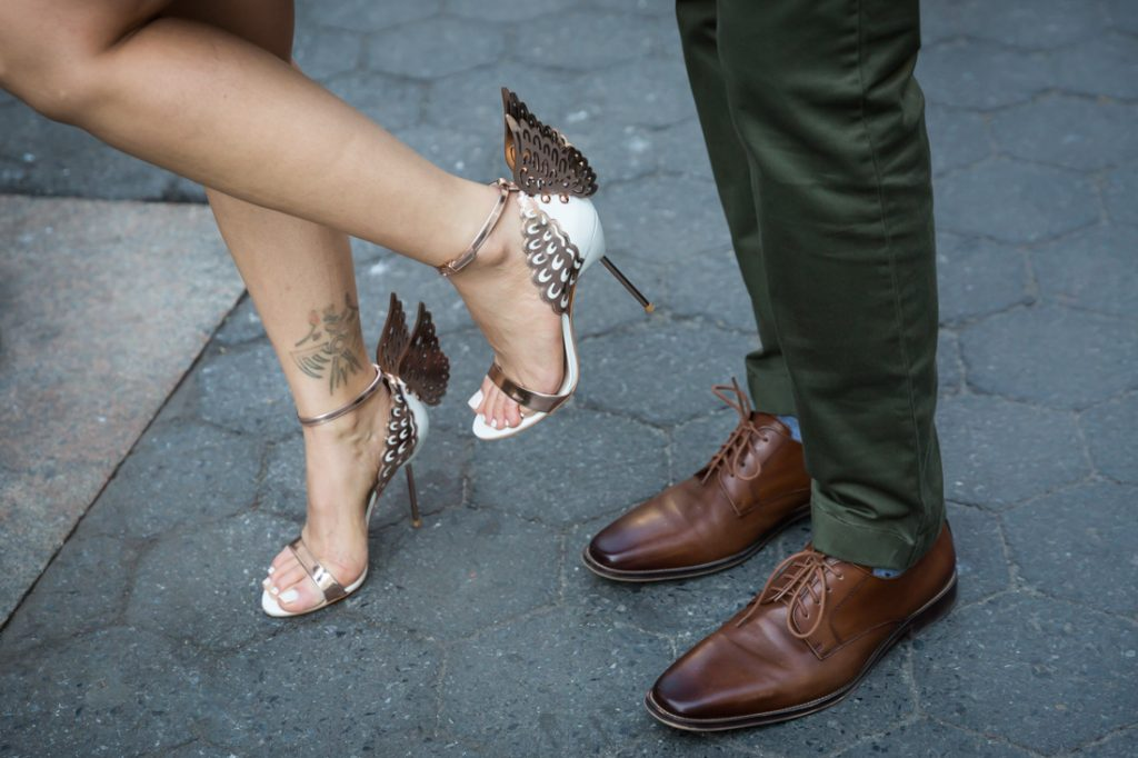 Close up on woman wearing winged sandals and man wearing brown shoes