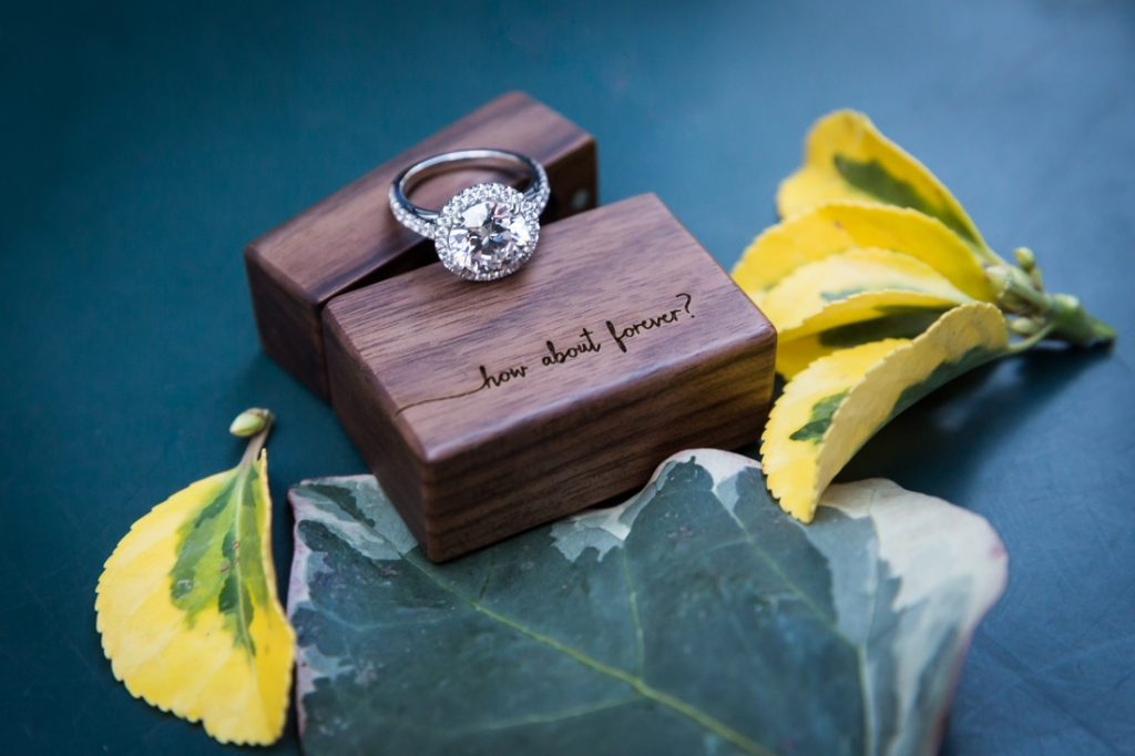 Close up of engagement ring, wooden box, and leaves