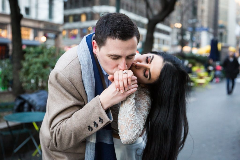 Man kissing woman's hand with engagement ring