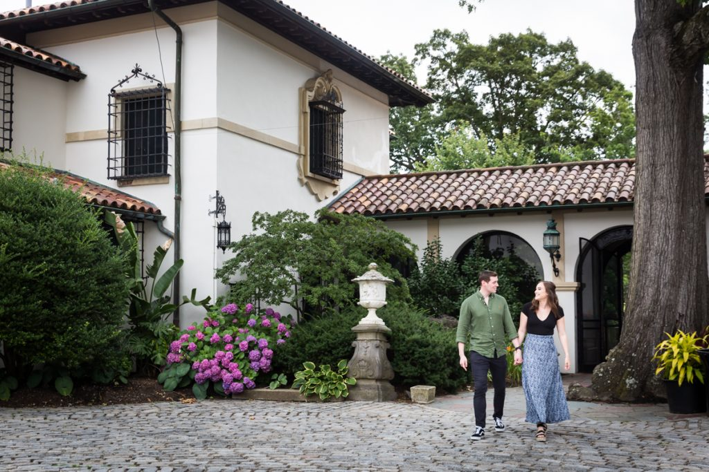 Vanderbilt Museum engagement photos of couple walking in courtyard