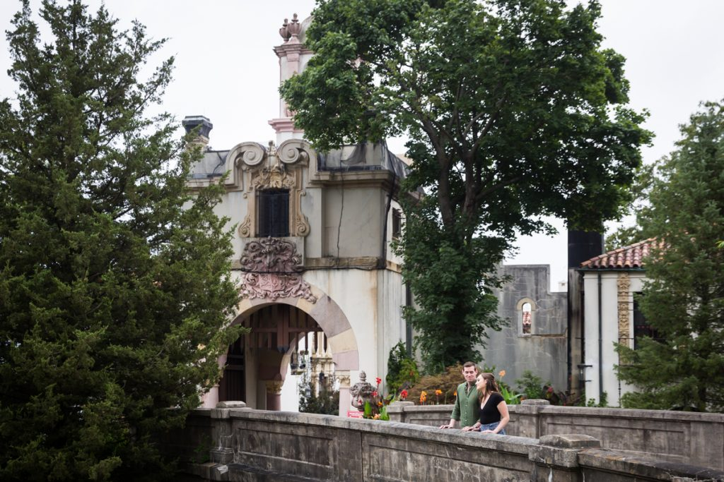 Vanderbilt Museum engagement photos of couple on bridge in front of stone gate