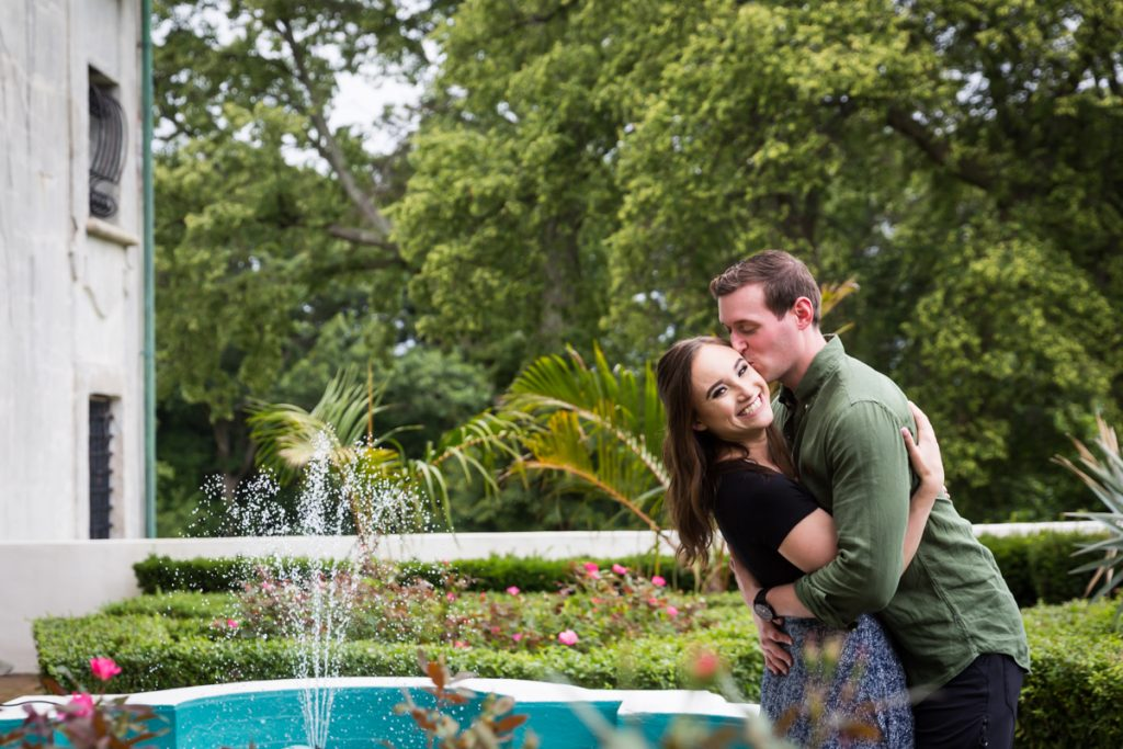 Man kissing woman on cheek in front of fountain at the Vanderbilt Museum