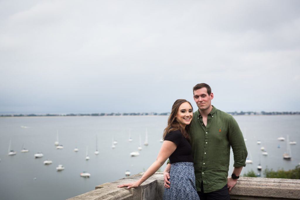 Couple in corner of railing with view of boats and bay in background