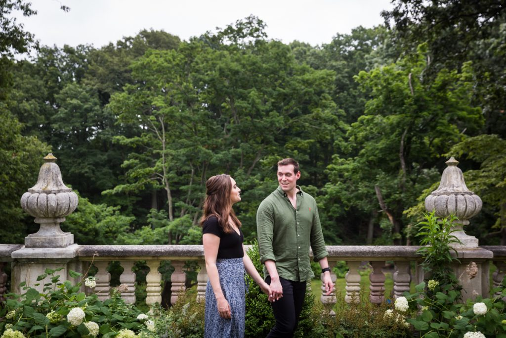 Vanderbilt Museum engagement photos of couple walking in front of stone railing and forest