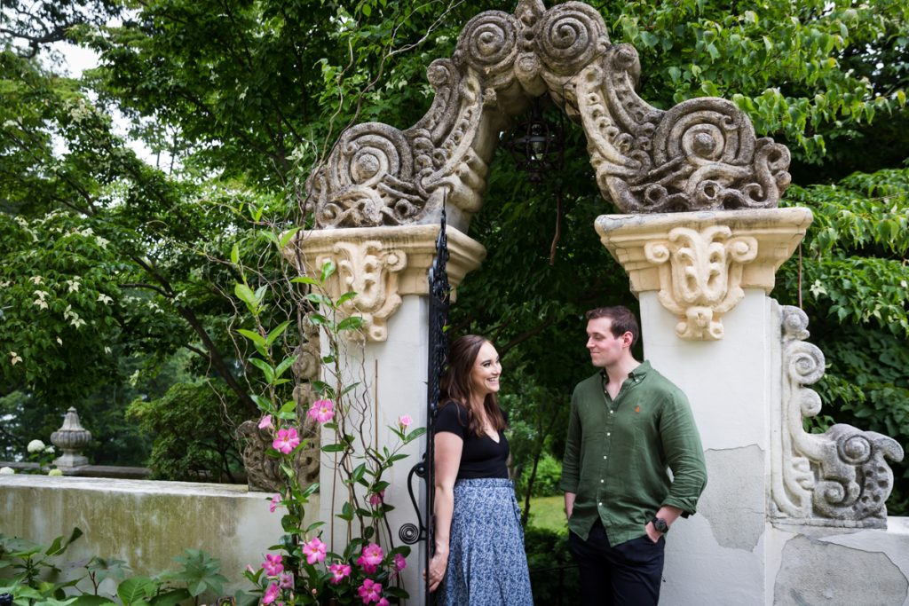 Couple standing in front of intricate gate at the Vanderbilt Museum