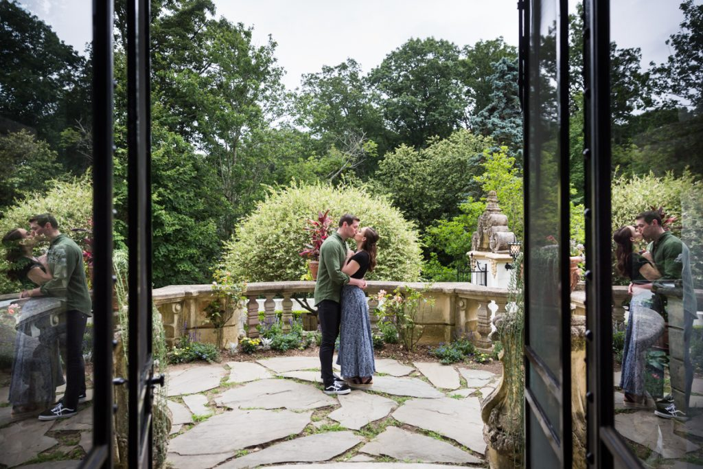 Couple hugging on patio reflected in glass doors at the Vanderbilt Museum