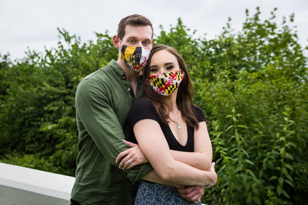 Vanderbilt Museum engagement photos of couple hugging while wearing face masks