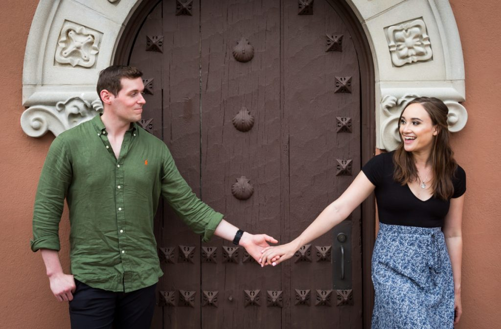 Couple holding hands in front of intricate wooden door at the Vanderbilt Museum