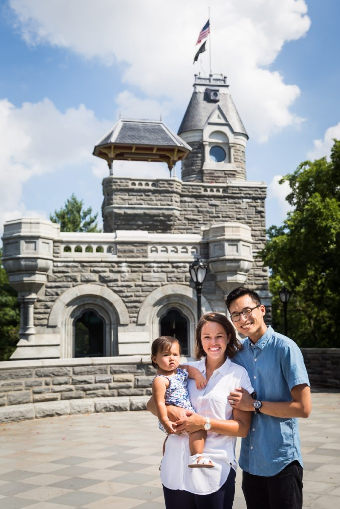 Parents holding toddler in front of castle turret during Belvedere Castle family portrait in Central Park