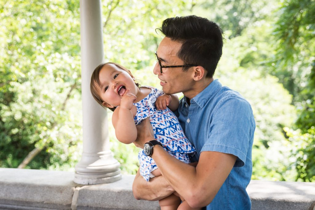 Father holding smiling baby during Belvedere Castle family portrait in Central Park