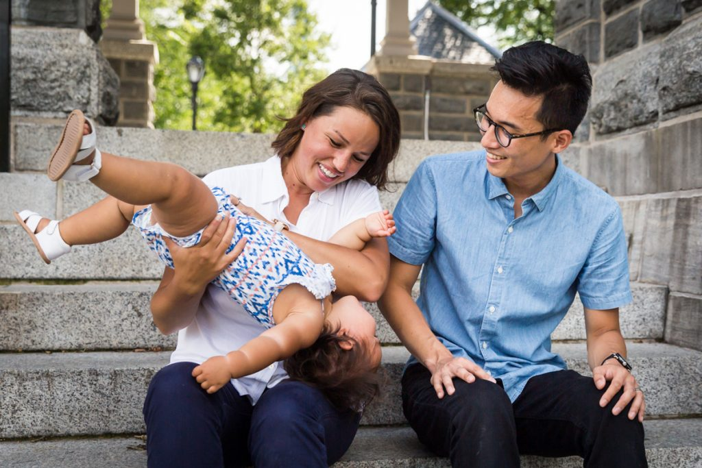 Parents holding squirmy toddler on steps of Belvedere Castle
