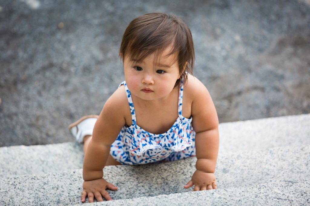 Baby girl crawling up steps of Belvedere Castle