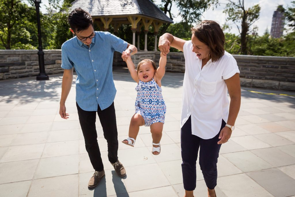 Mother and father swinging toddler by arms during Belvedere Castle family portrait in Central Park