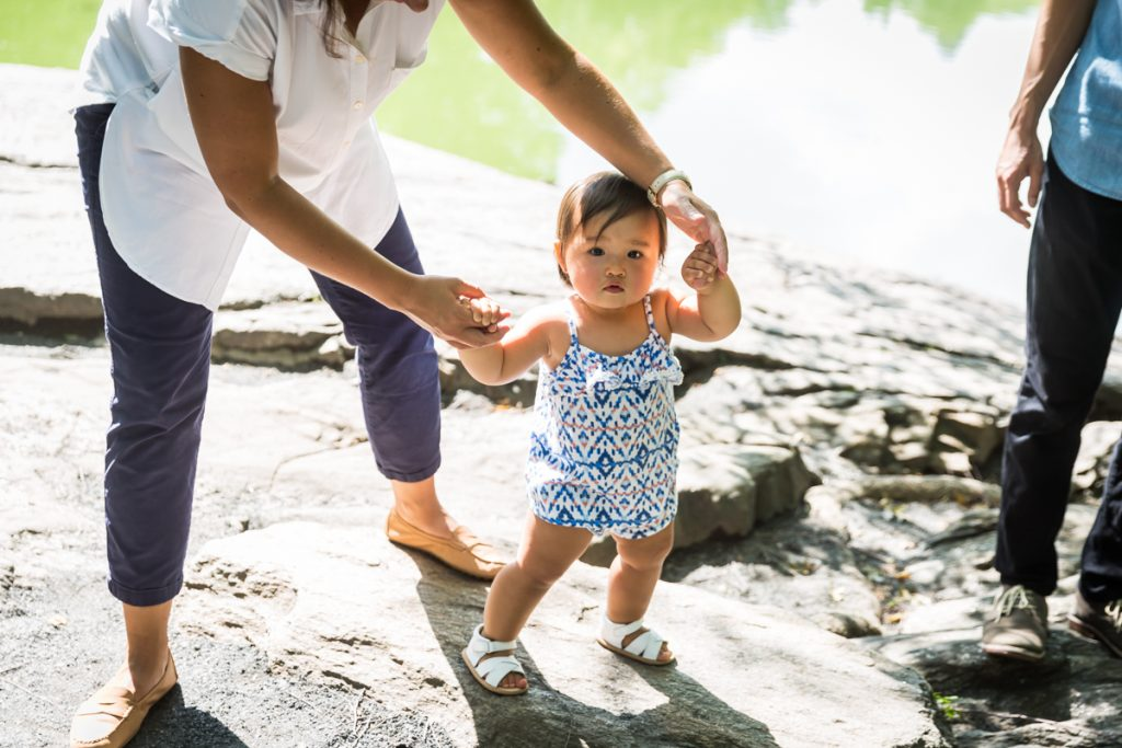 Mother helping baby girl walk on rock in Central Park